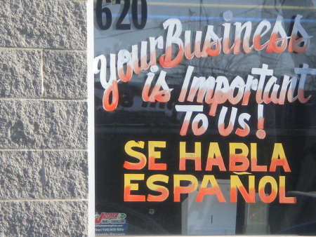A business promoting their good customer service with a sign saying Spanish Spoken Here.
